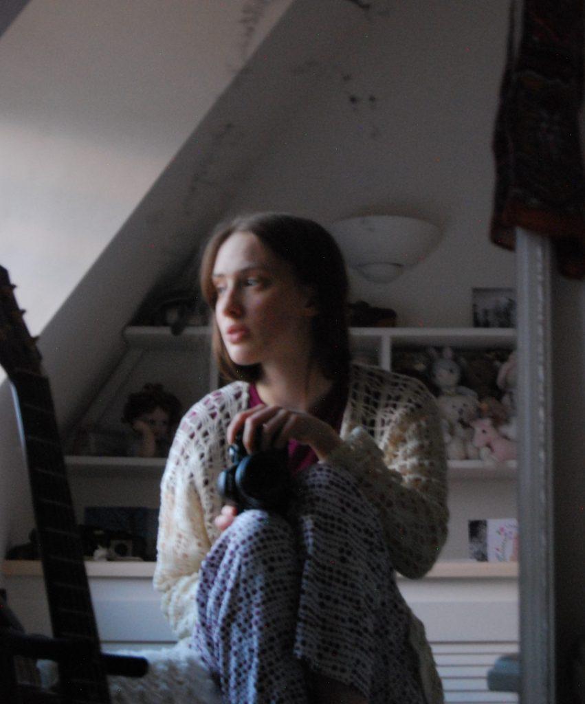 Photo taken in a mirror of a thoughtful looking white girl wearing pyjamas.