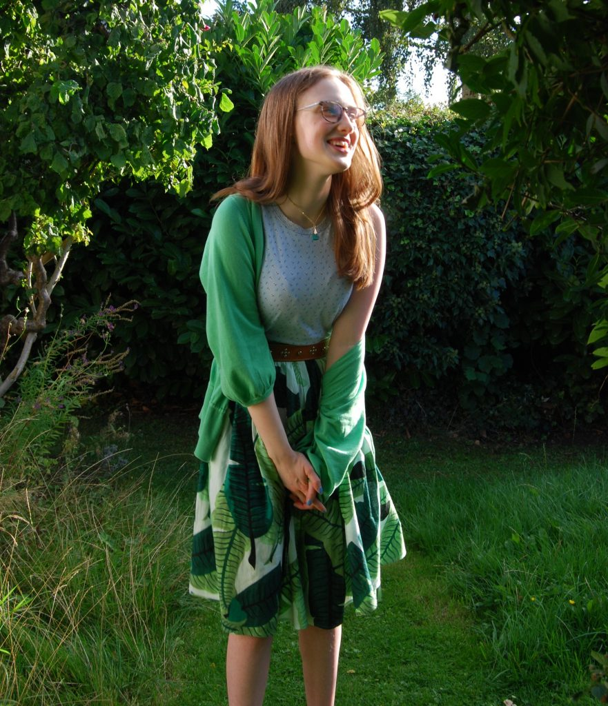 Sakara standing in the same garden as before, she's laughing.